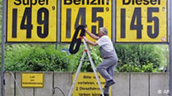 Man on ladder changing numbers on gas station sign