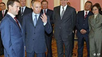 Russian President Dmitry Medvedev, left, and top officials, background, listen to Prime Minister Vladimir Putin
