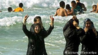 Four women wearing black burkinis - Islamic robes that cover the body and head and are made for swimming - wade into the crashing waves of an ocean. (Photo: Ismael Mohamad / dpa)