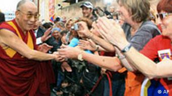 Crowds try to grab the Dalai Lama's hand as he is walking past them