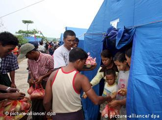 People hand food to cyclone victims standing in blue emergency shelter tents