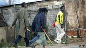 Three people walking outside a refugee camp in South Africa, one carrying a knife and another carrying a club