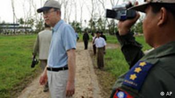 U.N. Secretary-General Ban Ki-Moon, left, is videotaped by a Burmese soldier