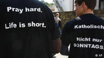 Two Catholics wearing T-shirts emblazoned with religious slogans