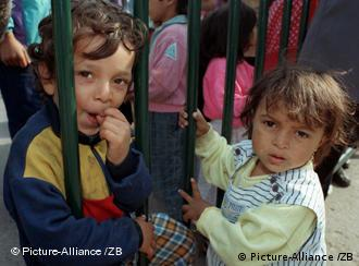 Two children hold on to a fence at an asylum center