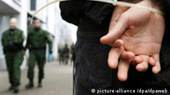 Hand-cuffed hands with two blurred police officers in the background