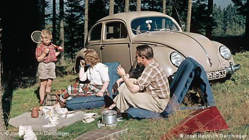 family having a picnic in front of their Volkswagen Beetle in the 1950s