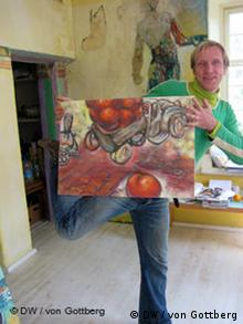 Man holding a painting while standing on one foot