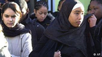 A schoolgirl adjusts her veil after class as she leaves a college north of Paris, surrounded by other students
