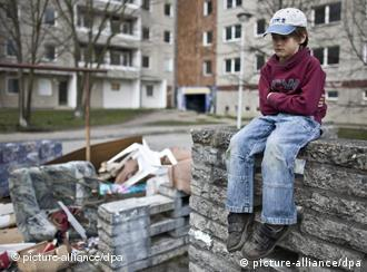 A boy sits on a wall next to trash outside an apartment complex