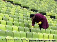 Мужчина убирает стадион