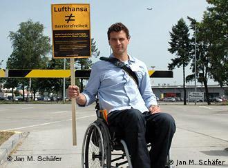 Macquarrie sitzt im Rollstuhl und hält ein Schild in der Hand: Lufthansa ist nicht barrierefrei