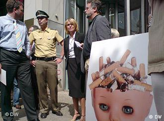 Marianne Tritz, a policeman and several other people are standing next to a picture of a baby doll's head filled with cigarette butts