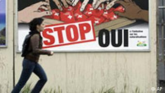 A woman runs past a billboard showing different colored hands reaching for Swiss passports and the word Stop
