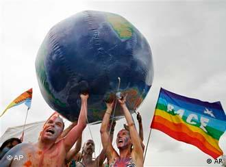 People hole up a globe with a peace flag in the background