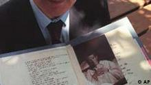 Dr. Konrad Maurer holds a turn-of-the-century medical file documenting the first case of Alzheimer's disease Thursday, July 17, 1997 in New York. It's like holding history in your hands, said Dr. Maurer of the file handwritten by Dr. Alois Alzheimer about a 51-year-old woman whose first symptom was jealousy toward her husband. Alzheimer's name identifies the disease suffered by millions of people whose severe loss of memory and comprehension he first described in daily notes about his patient. (AP Photo/Gino Domenico)