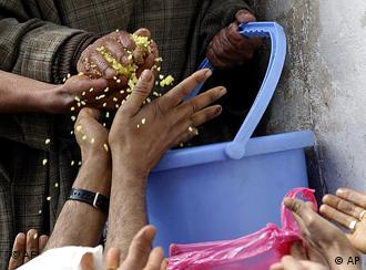 Hands reach for food handed out from a bucket