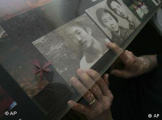 Ding Zilin, co-founder of the Tiananmen Mothers, a group representing families of those who died in the 1989 crackdown on pro-democracy demonstrations, arranges a photo of her son, Jiang Jielian, at her apartment in Beijing Wednesday June 4, 2008. Wednesday is the 19th anniversary of the military assault in which hundreds, possibly thousands, were killed as Chinese troops shot their way through the city to end weeks of protests in Tiananmen Square. Ding's 17-year-old son was killed in the assault. (AP Photo/Greg Baker)