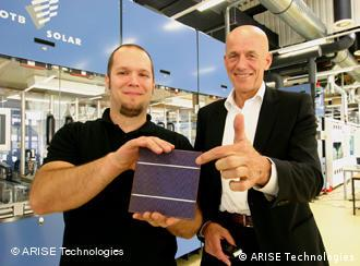 Sjouke Zijlstra and an employee hold a solar cell element in their hands