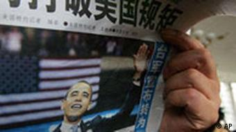 A man reads the Chinese Global Times newspaper which features a front page article about Barack Obama