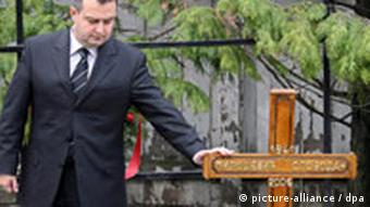 Ivica Dacic, president of former Serbian president Slobodan Milosevic's Socialists Party of Serbia (SPS) touches the wooden cross atop of Milosevic's grave
