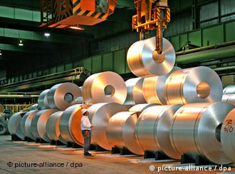 Man stands before steel coils
