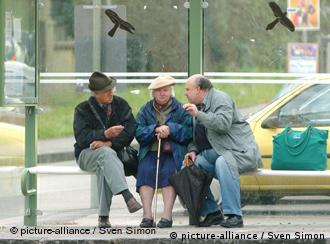 Three pensioners sitting at a bus stop