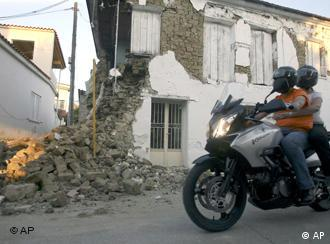 A couple on a motorbike pass by a destroyed house in Kato Ahagia, Greece, on Sunday June 8, 2008