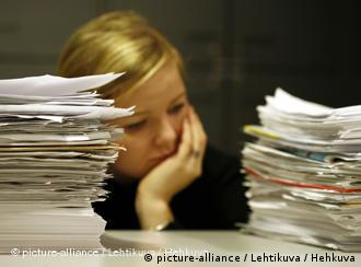 Woman sitting between two stacks of paper