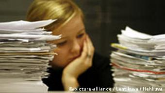 A woman with her head in her hands, behind stacks of paper