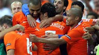 Netherlands' Giovanni van Bronckhorst, center, back to camera, celebrates with fellow team members after scoring during the group C match between the Netherlands and Italy