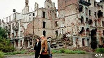 Local residents walk past destroyed buildings in Grozny, Chechnya, Russia, May 9, 2001.
