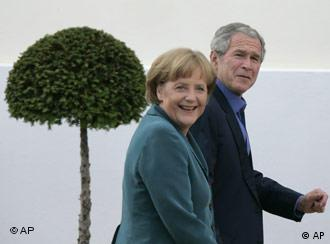 George W. Bush waves to cameras, flanked by Angela Merkel and Joachim Sauer (left) and his wife Laura Bush (right)
