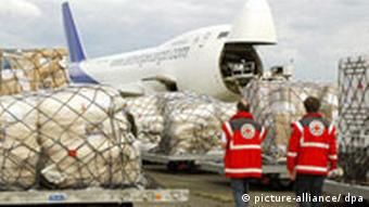 Two red cross workers and goods being loaded into an aircraft