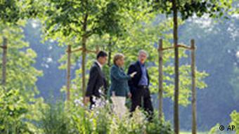 US President George W. Bush, right, German chancellor Angela Merkel, center, and Merkel's husband Joachim Sauer as they take a stroll in the park surrounding the government's guest house in Meseberg, Eastern Germany, Tuesday June 10, 2008.