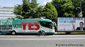 A cyclist passes by a 'YES' for Lisbon Treaty bus and a 'NO' for Lisbon truck in Dublin,