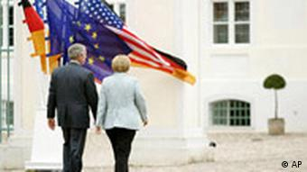 US President George W. Bush and German Chancellor Angela Merkel walk off after a press conference at Schloss Meseberg
