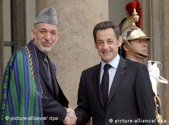 Afghan President Hamid Karzai shakes hands with French President Nicolas Sarkozy