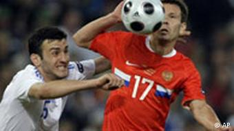 Russia's Konstantin Zyrianov is challenged by Greece's Vassilis Torosidis,