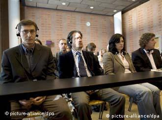 Mehrere Personen hinter einem Tisch in einem Saal (16.6.08, Den Haag - Niederlande, Quelle: dpa)