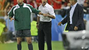 Germany's head coach Joachim Loew, center, and Austria's head coach Josef Hickersberger, right, argue with the match's fourth official Damir Skomina