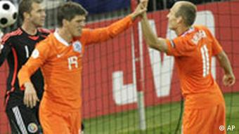 Netherlands' Klaas-Jan Huntelaar, foreground left, celebrates scoring the opening goal with his teammate Arjen Robben, right, as Romania's Bogdan Lobont looks on during the group C match between the Netherlands and Romania in Bern