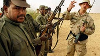 A U.S. Special Forces Green Berets, right, inspects the weapons of Malian soldiers from the 512th Motorised Infantry company during an ambush training exercise in the desert near Timbuktu, Mali Wednesday, March 17, 2004. The training is part of the U.S. Pan-Sahel Initiative which aims to help soldiers in Mali, Niger, Chad and Mauritania boost battle skills amid the worldwide fight against terrorism. (AP Photo/Ben Curtis)