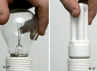 A traditional bulb and an energy-saving bulb being screwed in to a socket