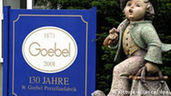 A large Hummel figure next to a Goebel sign