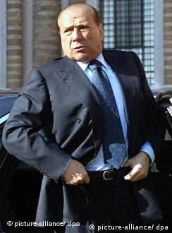 Silvio Berlusconi tucks his shirt in