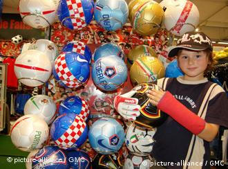 A boy holds up Euro 2008 merchandising including footballs