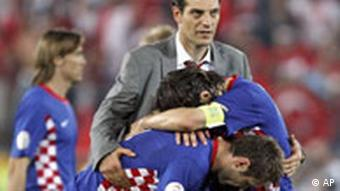 Croatia's head coach Slaven Bilic, top, comforts his players Niko Kovac, right, and Robert Kovac after the penalty shoot out of the quarterfinal match between Croatia and Turkey in Vienna, Austria, Friday, June 20, 2008, at the Euro 2008 European Soccer Championships in Austria and Switzerland. Turkey defeated Croatia 3 penalties to 1 in the final penalty shoot out. (AP Photo/Jon Super)