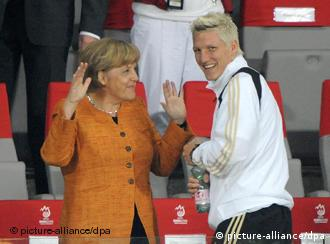 German Chancellor Angela Merkel (L) and Bastian Schweinsteiger