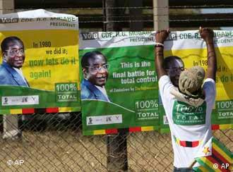 A supporter of Zimbabwean leader Robert Mugabe posting campaign posters to a perimeter fence in Harare